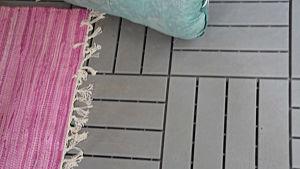 Grå plattor på ett golv, en rosa matta på.