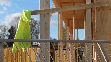 En gul tröja vid ett husbygge.
