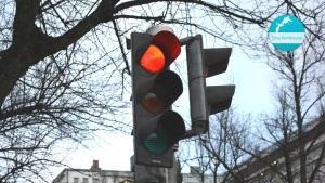 Närbild på ett trafikljus som lyser rött. I övre högra hörnet av bilden finns det en rund, blå etikett där det står Dina hemknutar.
