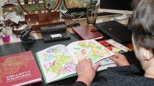 Nainen selaa tekemäänsä värityskirjaa.