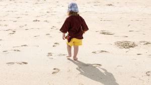 Ett barn på en sandstrand.