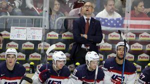 Jeff Blashill står och tittar upp, framför honom sitter några spelare på bänken