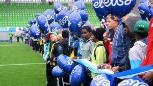 Juniorfotbollsspelare med ballonger på rad på fotbollsplan när Sandvikens stadion invigs.