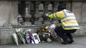 En polis lägger ner blommor vid Whitehall i London.