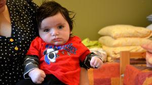 Ett spädbarn sitter i en kvinnas famn, barnet stirrar rakt in i kameran.