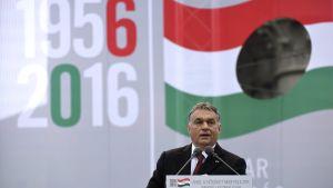 Viktor Orban med den ungerska flaggan och årtalen 1956 och 2016 i bakgrunden. Orban talar på en minnesceremoni för Ungernrevolten 1956
