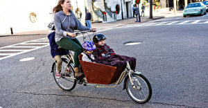 En kvinna cyklar men två barn sittandes fram i en korg och ett barn på pakethållaren.