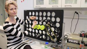 Tutkija Suvi Arola selluloosakuitua käsittelevän laitteen edessä.