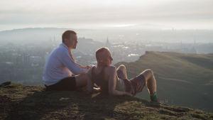Renton (Ewan McGregor) och Spud (Ewen Bremner) sitter uppe på ett berg och tittar ut över Edinburgh.
