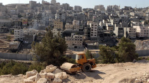Byggarbete på israeliska bosättningar i östra Jerusalem och muren som separerar israeliska och palestinska områden och palestinska bostadsområden i bakgrunden.