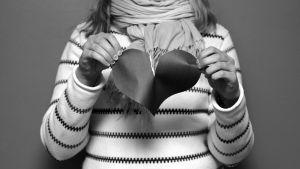 Flicka river pappershjärta i två, svartvit