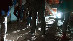 Starkt motljus som lyser upp flera par ben i ett mörkt utrymme.