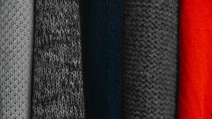Stickade tröjor som hänger bredvid varandra i garderob, närbild.