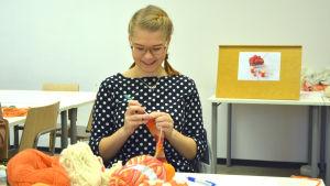 Veronica Lönnqvist sitter i ett klassrum och stickar, framför sig har hon en hög av olika garn