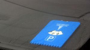 På bilden finns en blå parkeringsskiva.