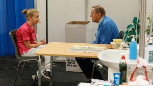 Närvårdare Madelen Grankulla och en äldre man sitter vid ett bord och diskuterar.