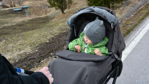 Linda Sundberg knuffar sonen Rufus i barnvagn längs Vålaxvägen