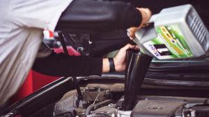 Person fyller på motorolja