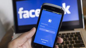 Smarttelefon där inloggning till Facebook visas på skärmen. I bakgrunden en datorskärm där man ser texten Facebook.