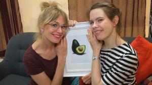 Två leende kvinnor sitter i en soffa med en bild på en avocado mellan sig.