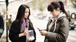 Kvinna betalar med mobilappen Shwish i stället för med kontanter.
