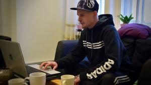Alex Granqvist sitter i en soffa och använder dator.