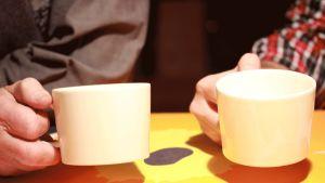 Två kaffekoppar och två händer.