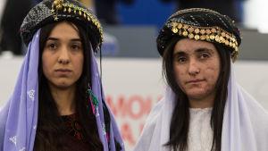 Nadia Murad till vänster, Lamiyja Aji Bashar till höger. De är klädda i yazidiernas traditionella dräkt med en slköja över huvudet samt ovanpå en hatt med guldslantar sydda runt brättet.