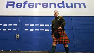 """En man i skotsk kilt går förbi en skylt där det står """"Referendum"""""""