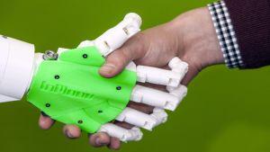 En robothand som skakar hand med en människohand.
