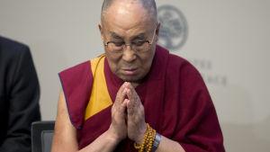 Dalai Lama i röd och gul klädsel ber för offren i Orlando medan han deltar i en direktsänd stream från United States Institute of Peace i Washington om hur man kunde förhindra och stoppa våld.
