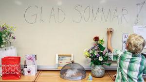 """Skolelev skriver """"glad sommar"""" på en tavla i skola."""