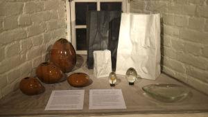 Olika föremål som Tapio Wirkkala designat för tyska Rosenthal. Föremålen är utställda på en utställning.