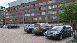 Ett höghus i sex våningar i rödbrunt tegel sett framifrån. Framför i bilden syns parkeringsrutor varav ungefär hälften är upptagna av vanliga personbilar.