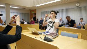 Sebastian Tynkkynen, före detta ordförande för Finsk Ungdom, i rätten åtalad för hets mot folkgrupp. Tynkkynen bad om liv för att foografera och filma rättegången.