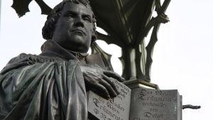 Staty i Wittenberg föreställandes Martin Luther med Nya testamentet skriven på tyska uppslaget i sina händer