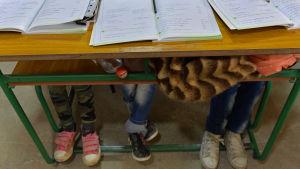 Syriska flyktingbarn i skola i Libanon. Tre par barnfötter under en skolbänk med skolböcker på.