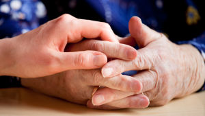 händer. en äldre persons knäppta händer och så en yngre människas hand ovanpå