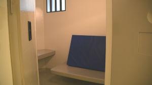 Bild in mot cell i häkte. Bord, brits med blå madrass, litet fönster med galler.
