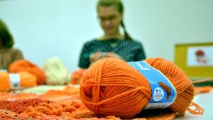 Ett orange garnnystan, i bakgrunden syns en ung kvinna suddigt