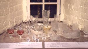 En mängd olika glasföremål designade av Tapio Wirkkala utställda i en fönsternisch.