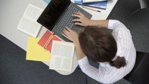 En kvinna studerar och skriver på datorn.