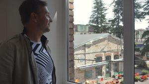 Raimo Matvere tittar ut över Telliskiviområdet genom ett fönster.