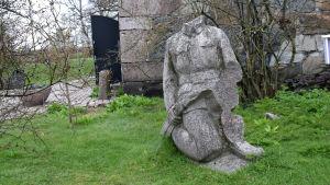 En skulptur som ser ut som en soldat men utan huvud står i en trädgård.