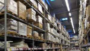 Lagerlokal med varor förpackade i pappkartonger på olika hyllplan ovanför varandra.