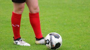 En person står bredvid en fotboll.