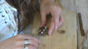 Närbild på Sharlena Lahtinens händer när hon rör med en tång i ett smycke gjort av ett gammalt kugghjul med pärlor på.