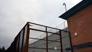 Staket, taggtråd och övervakningskameror vid fängelsemur.