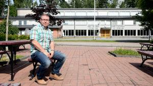 Man sitter på en röd bänk framför en rappad skolbyggnad.