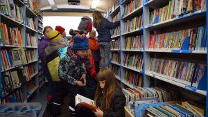 Skolbarn inne i bokbuss